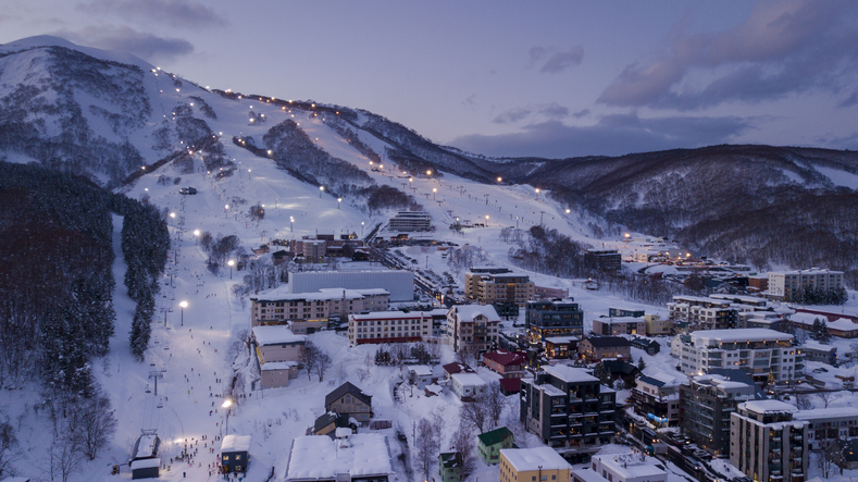 Aerial view at dusk of night skiing in Niseko Village, a popular destination for ski resorts in Japan